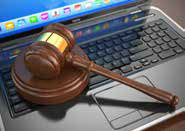 Laptop with a gavel on top of the keyboard